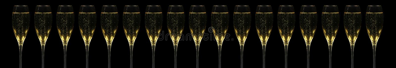 Champagner Flutes. Very long banner with 17 champagner flutes in a row over black royalty free stock photo