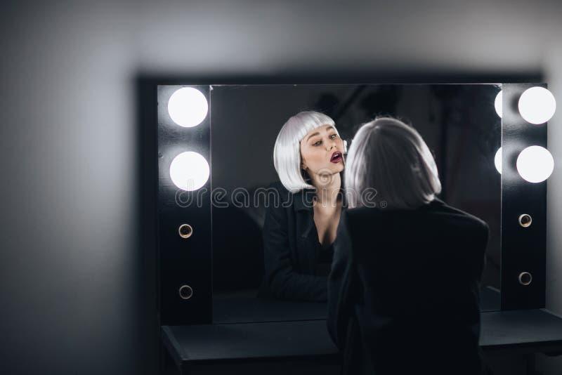 Champanhe bebendo da mulher loura sedutor e vista do espelho imagem de stock royalty free
