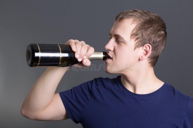 Download Champanhe Bebendo Do Homem Novo Sobre O Cinza Foto de Stock - Imagem de viciado, conceito: 29828276