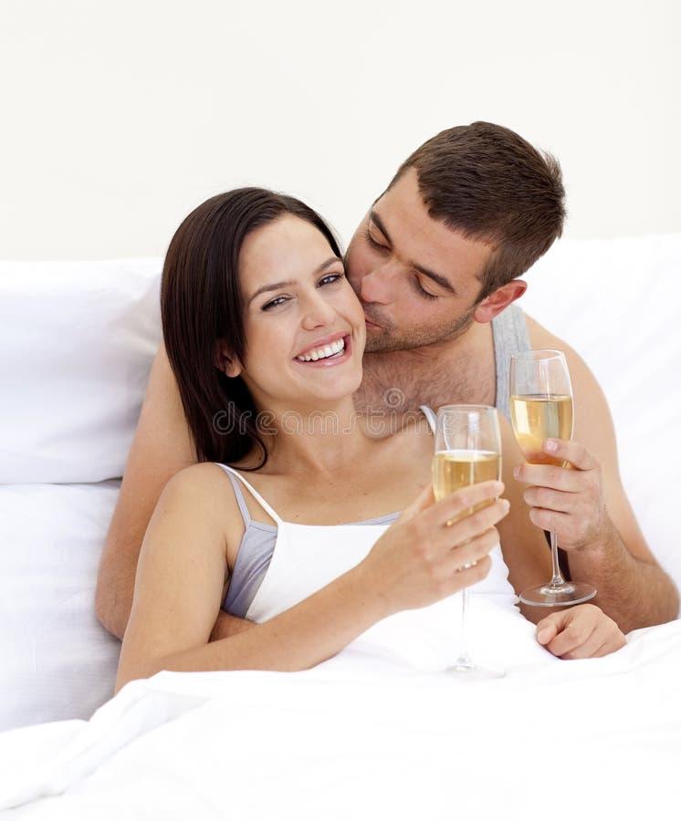 Champanhe bebendo dos pares na cama foto de stock royalty free