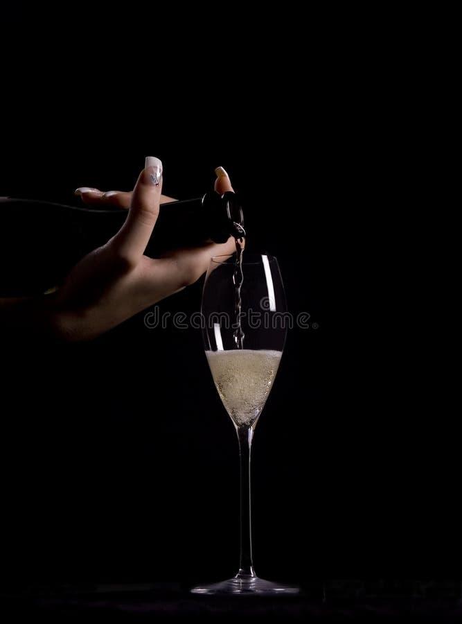 Champanhe de derramamento da mulher imagem de stock royalty free