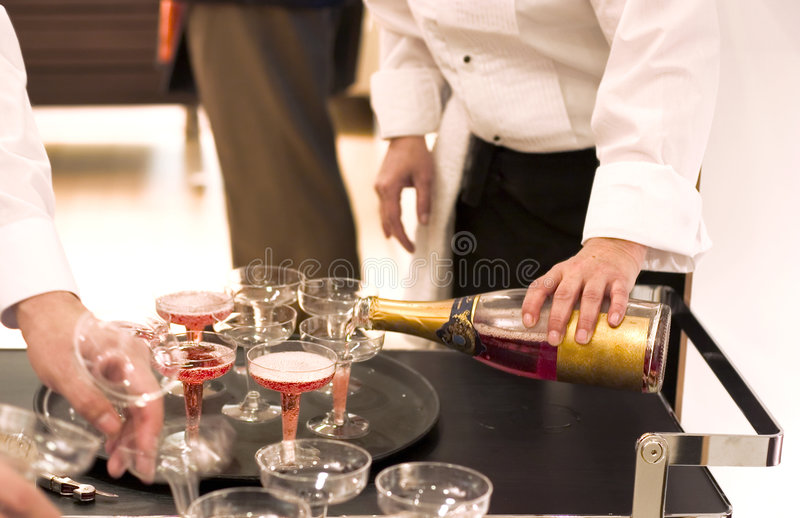 Champanhe de derramamento do empregado de mesa imagens de stock