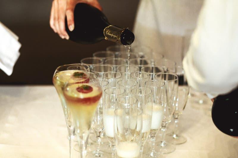 Champanhe de derramamento do garçom elegante nos vidros na cerimônia de casamento foto de stock royalty free