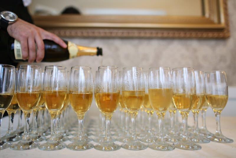 Champanhe de derramamento do garçom em muitos vidros imagens de stock