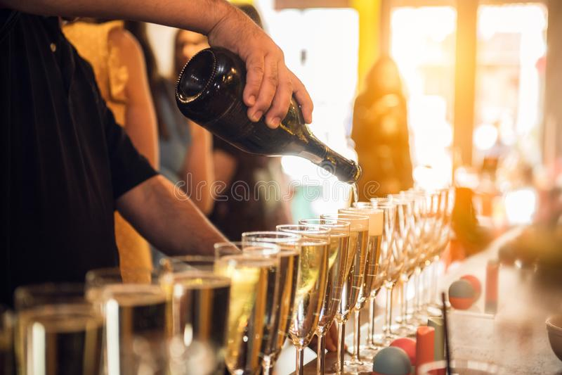Champanhe de derramamento do garçom em vidros no evento do partido na barra foto de stock