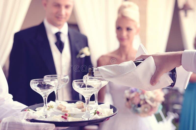 Champanhe de derramamento do garçom nos vidros fotos de stock royalty free