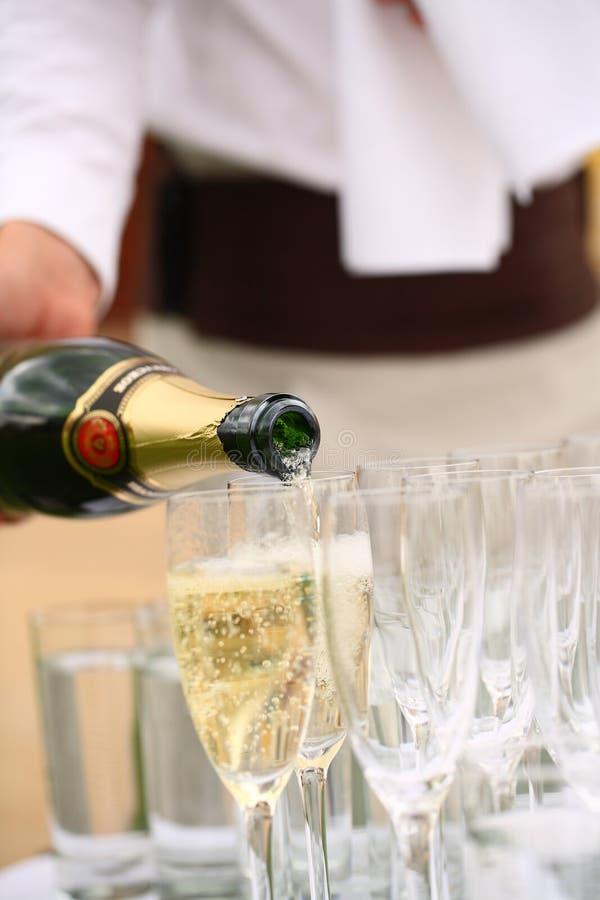 Champanhe de derramamento do garçom nos vidros na tabela imagem de stock