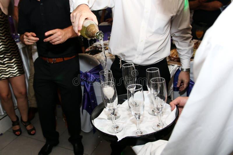 Champanhe de derramamento do garçom nos vidros no casamento fotos de stock