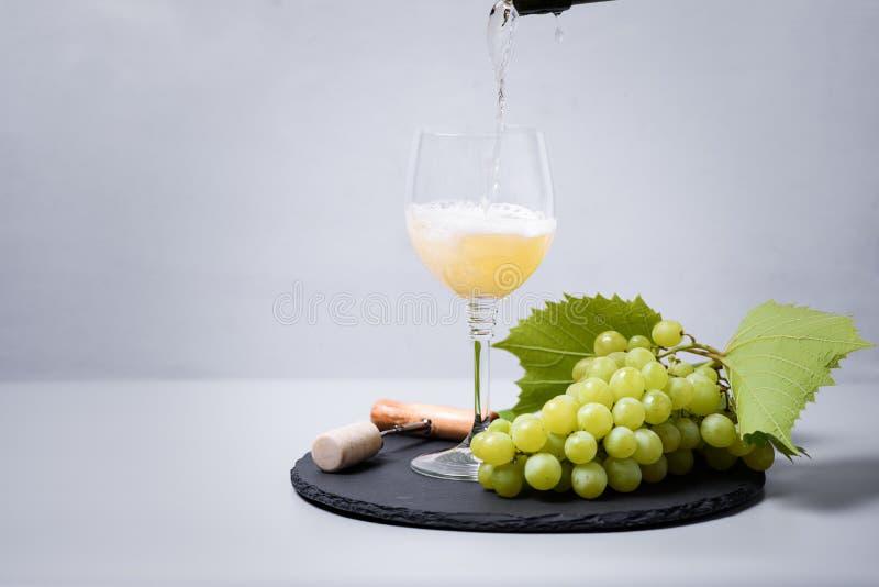 Champanhe de derramamento do vinho branco da garrafa no copo de vinho no fundo cinzento Conceito da celebra??o do feriado imagem de stock