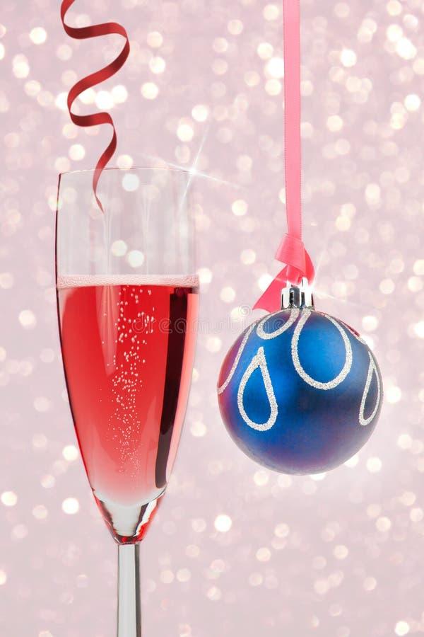Champanhe efervescente e quinquilharia contra luzes de Natal imagens de stock