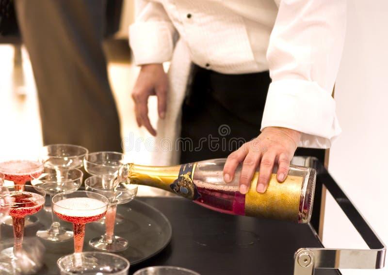 Champanhe pooring do empregado de mesa imagem de stock royalty free