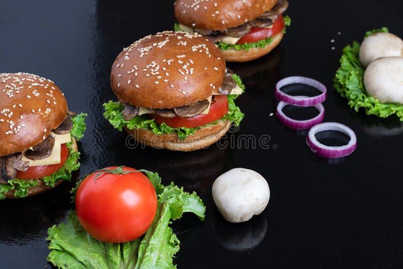 champginons crus e anéis de cebola vermelha com hamburgueres do cogumelo fotografia de stock