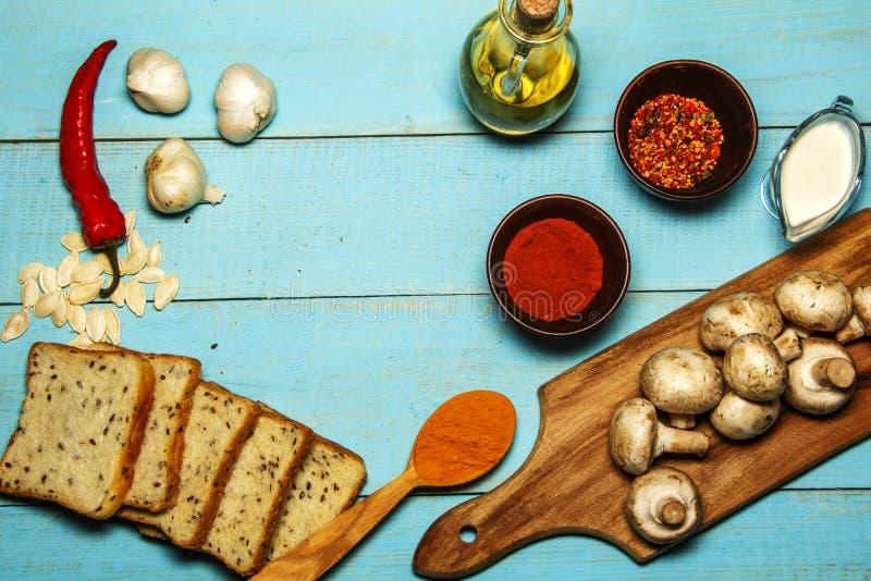 Champiñones de la seta, ajo, pimienta, cardamomo, salsa de crema agria, aceite de oliva, pan en un fondo hermoso de madera Visión imagen de archivo libre de regalías