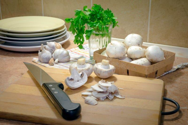 Champiñones fino cortados y cocinado con aceite, ajo y parsle imágenes de archivo libres de regalías