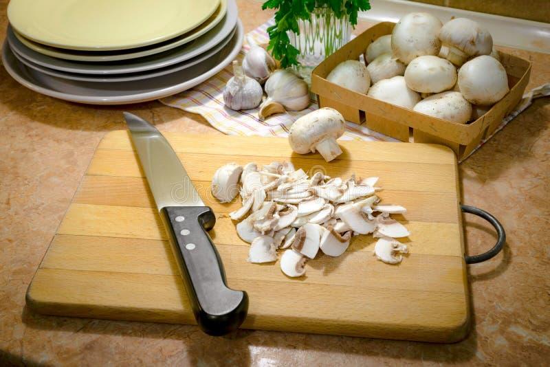 Champiñones fino cortados y cocinado con aceite, ajo y parsle imagenes de archivo
