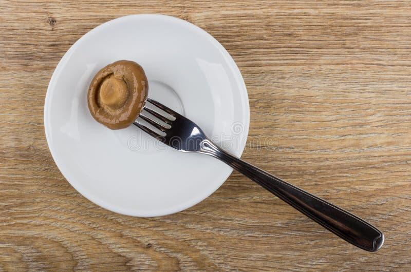 Champignon ficelé sur la fourchette dans la soucoupe blanche sur la table en bois photos stock