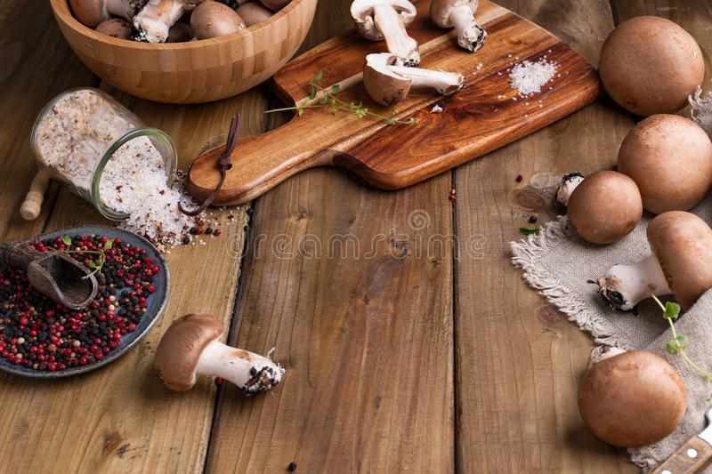 Champignon mushrooms with red onions and spices on a wooden background, wooden utensils. Rustic style photo. Vegetarian lunch of. Vegetables. Place for text b royalty free stock image