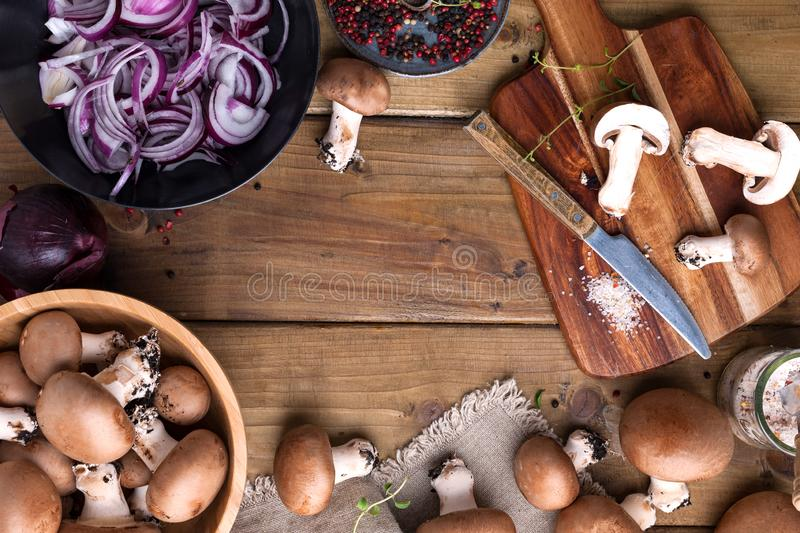 Champignon mushrooms with red onions and spices on a wooden background, wooden utensils. Rustic style photo. Vegetarian lunch of. Vegetables. Place for text b stock images