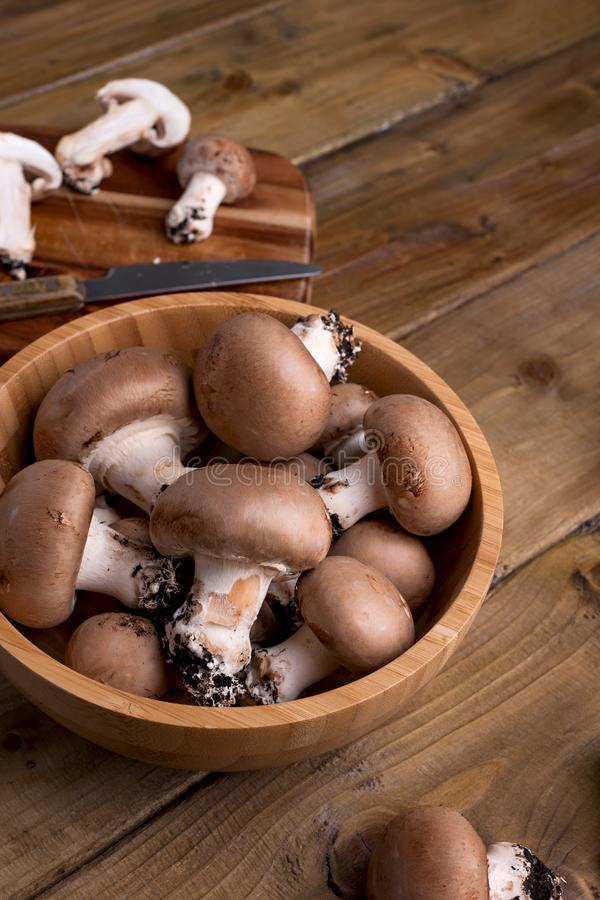 Champignon mushrooms with red onions and spices on a wooden background, wooden utensils. Rustic style photo. Vegetarian lunch of. Vegetables. Place for text n stock image