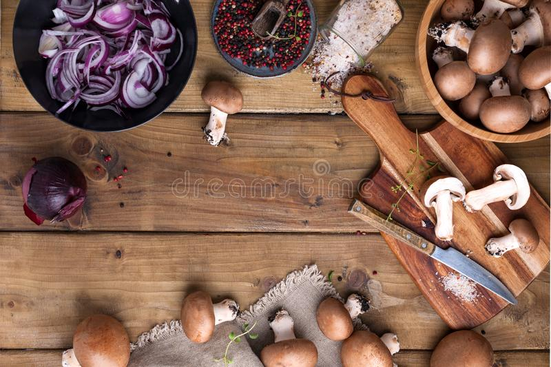 Champignon mushrooms with red onions and spices on a wooden background, wooden utensils. Rustic style photo. Vegetarian lunch of. Vegetables. Place for text royalty free stock photos