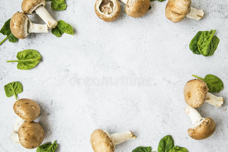 Champignon mushrooms with spinach leaves frame on concrete background with copy space , top view royalty free stock photography