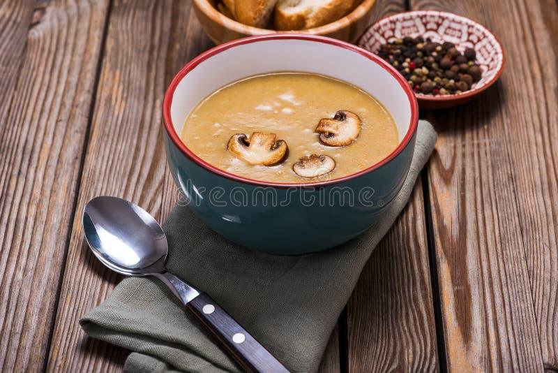 Champignonkrämsoppa över lantlig träbakgrund, läcker grönsaksoppa, sund vegetarian och strikt vegetarianmat arkivbild