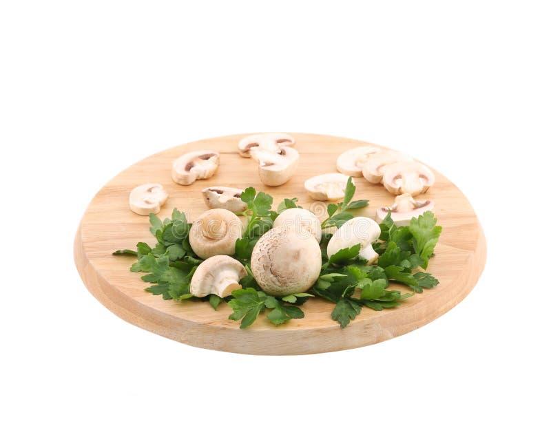 Champignons blancs sur le conseil en bois photos stock