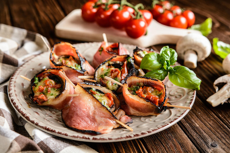 Champignons bourrés du fromage, tomates séchées au soleil et enveloppés en lard images stock