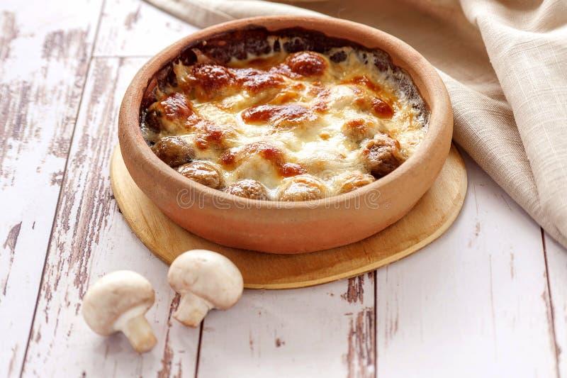 Champignons cuits au four avec du fromage sur la poterie de terre photo libre de droits