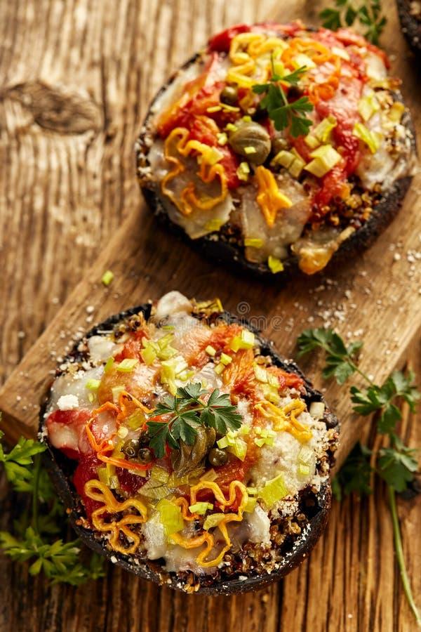 Champignons cuits au four de portobello bourrés du quinoa, des légumes et du fromage avec des herbes sur un conseil en bois, nour photos stock
