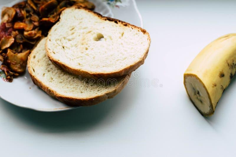 Champignons cuits et deux morceaux de pain images stock