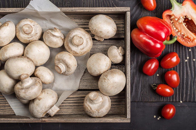 Champignons dans une boîte en bois et des légumes photographie stock libre de droits
