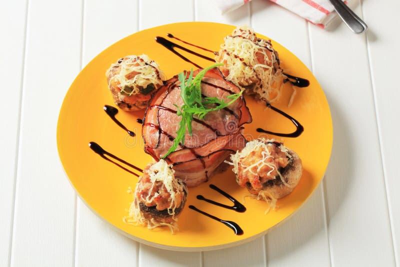Champignons de couche bourrés et filet lard-enveloppé de porc photographie stock libre de droits
