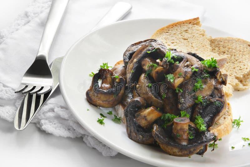 Champignons de couche sur le pain grillé images stock