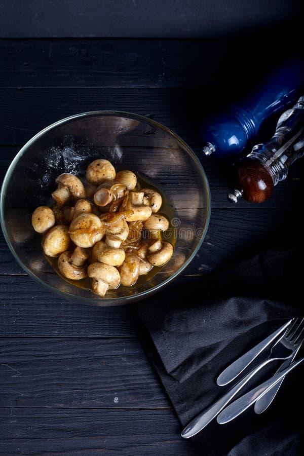 Champignons de marinade sur le backgorund foncé image stock