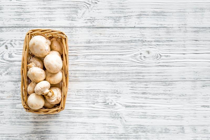 Champignons de paris de champignon Champignons de paris entiers crus frais dans le panier sur l'espace en bois gris de copie de v photos libres de droits