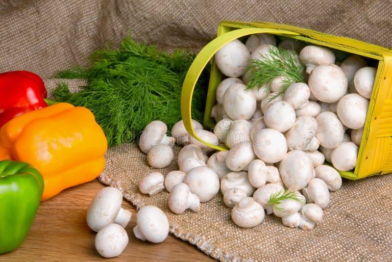 Champignons de paris dans un panier, avec des légumes sur la table photographie stock libre de droits