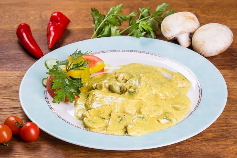 Champignons in einer Soße Teller mit Frischgemüsesalat lizenzfreies stockbild