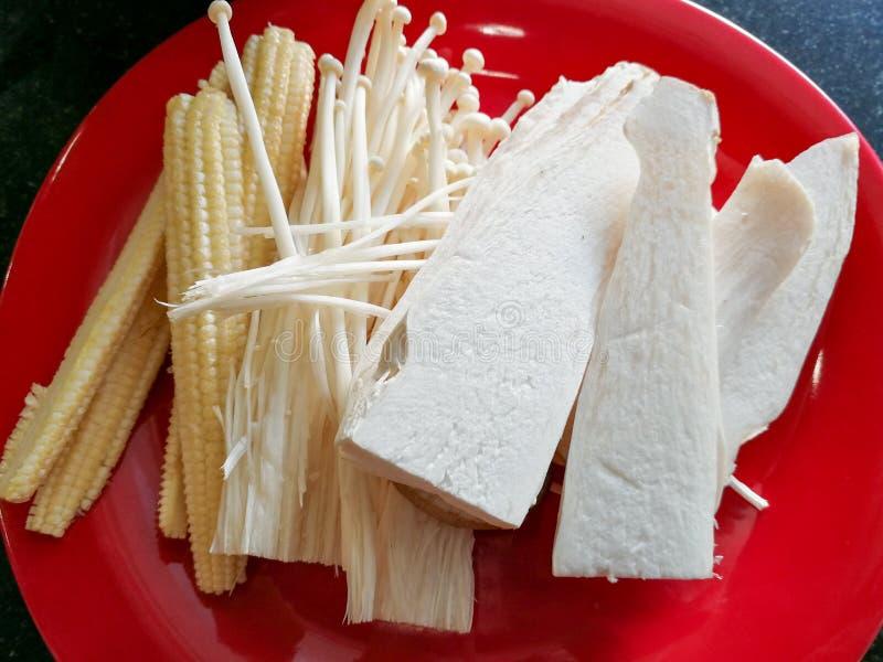 Champignons et maïs sur plaque rouge au restaurant photo stock