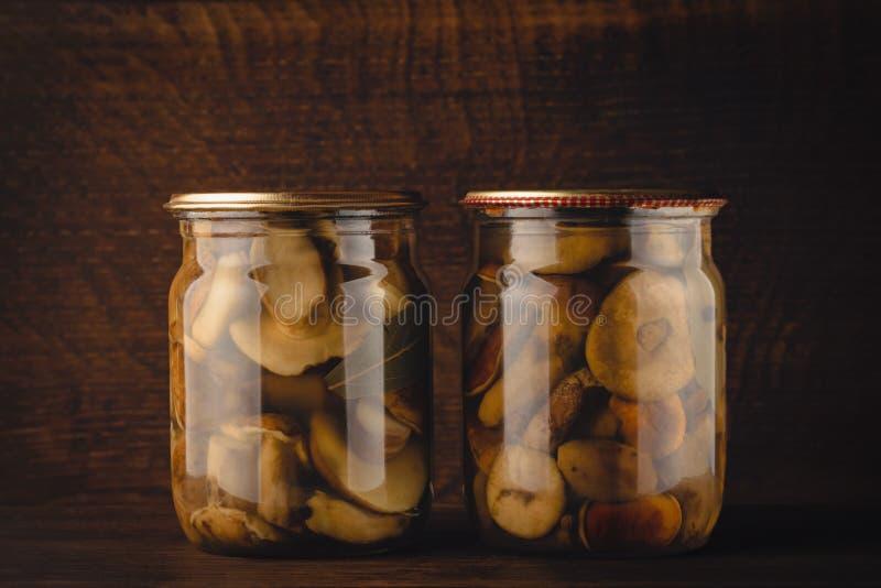Champignons sauvages faits maison marinés sur une étagère en bois images stock