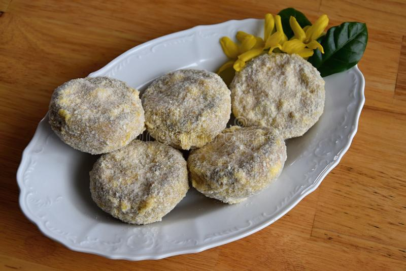 Champignons som är välfyllda med en blandning av ost och korven på en platta som är dold med i brödsmulor och mjöl arkivbild