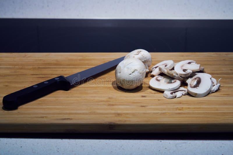 Champinjoner klippte nytt in i skivor med en kniv och som f?rlade p? ett tr?br?de som f?rbereddes f?r att laga mat i k?ket royaltyfri fotografi