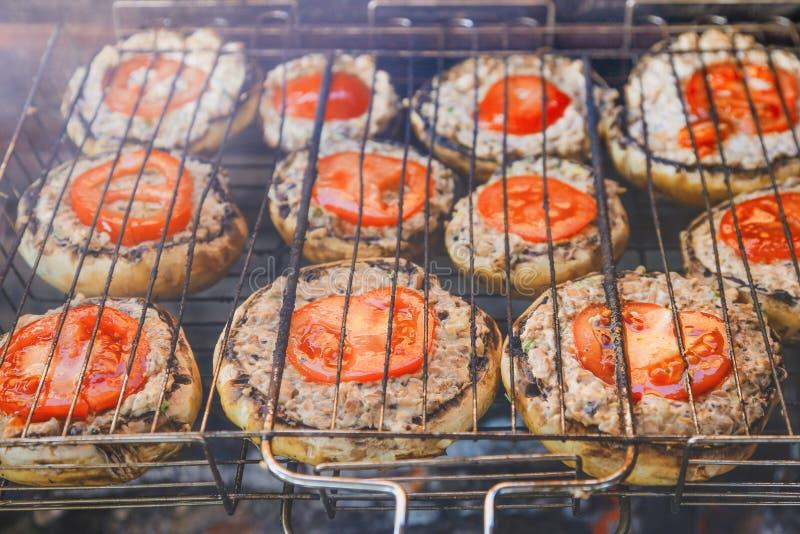 Champinjoner med tomater som grillas på gallret royaltyfria foton