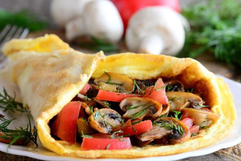 Champinjoner, omelett för tomatomelettfrukost som är välfylld med champinjoner, tomater och dill på en platta och en gammal träba royaltyfri fotografi