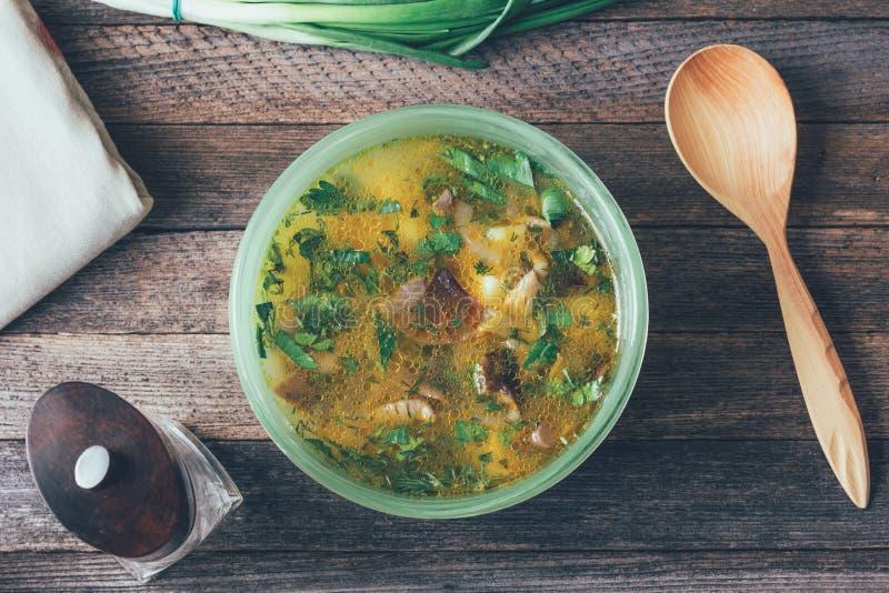 Champinjonsoppa i maträtten, salladslökarna, träskeden och en peppar maler på den gamla trätabellen arkivbilder