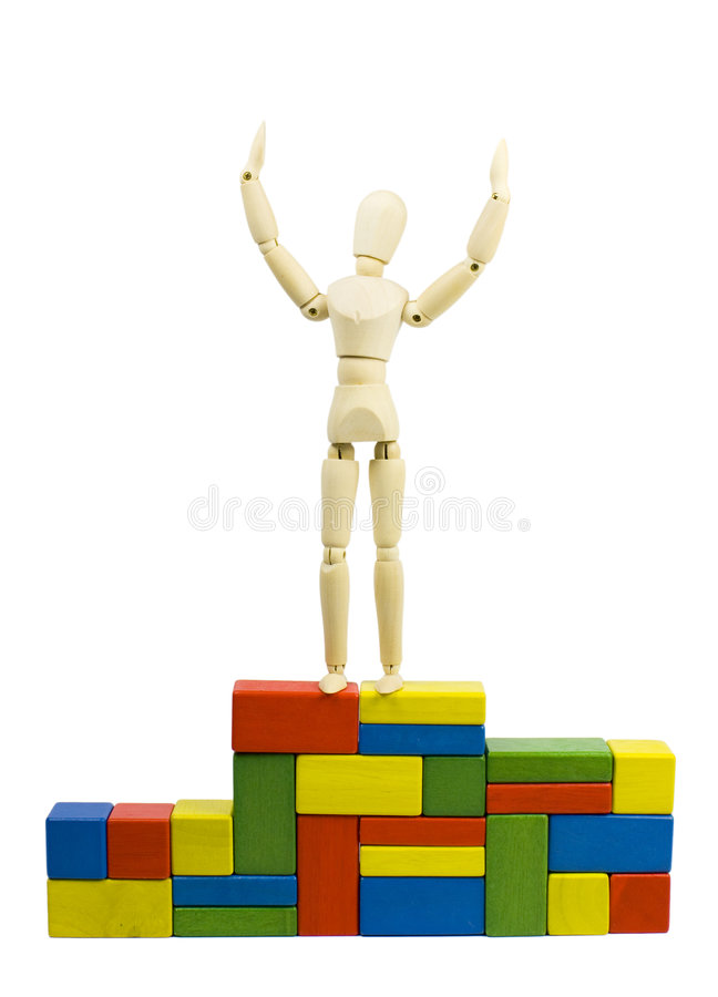 Champion. A wooden mannequin figurine standing on the winner platform built of colorful wooden toy blocks, happy for victory - champion concept stock image