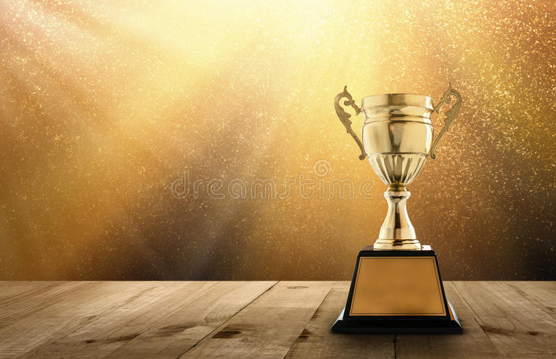 champion golden trophy on wood table with copy space and gold Twinkly Lights and glitter stars light background copy space ready stock image