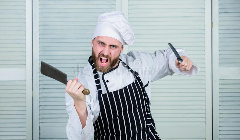 He is a champion in the kitchen. angry bearded man with knife. love food. cook in restaurant. chef ready for cooking. Confident man in apron and hat royalty free stock images
