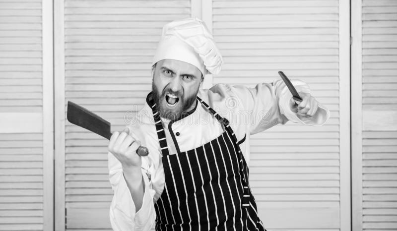 He is a champion in the kitchen. angry bearded man with knife. love food. cook in restaurant. chef ready for cooking. Confident man in apron and hat stock photos