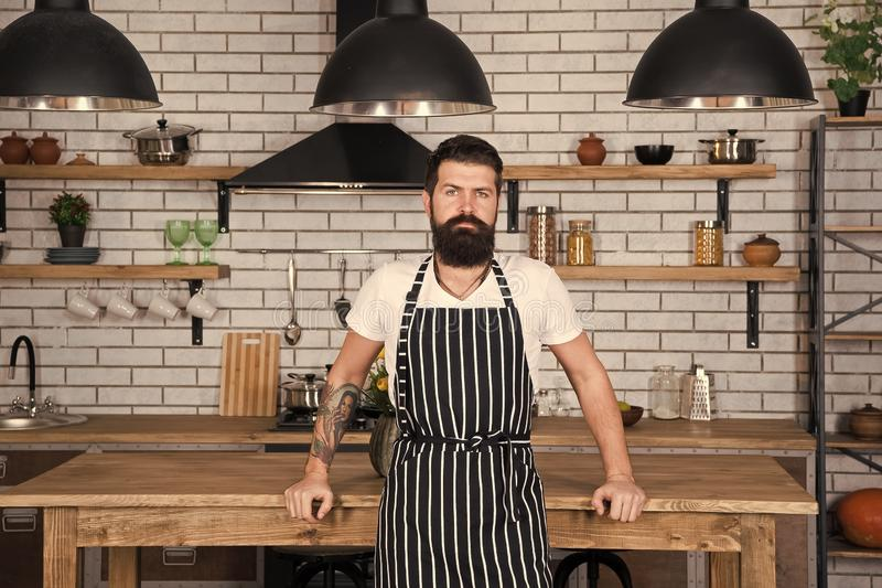 He is a champion in the kitchen. Hipster in kitchen. Mature male. Bearded man cook. Bearded man in apron. Man chef. Cooking. Restaurant or cafe cook. Lunch time royalty free stock photos